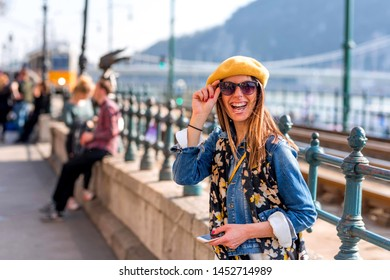 A cheerful young woman enjoying the spring in the center of a European city.