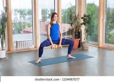Cheerful young woman  exercising with dumbbells in the home