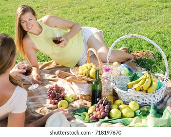 Cheerful young woman with friend sitting on green lawn drinking wine on picnic in park