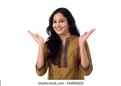 Cheerful young woman gesturing an open hands against white background