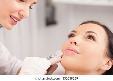 Cheerful young woman is getting botox procedure. The doctor is standing near her and smiling. She is holding syringe and touching it to female face