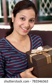 Cheerful young woman with gift box