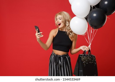 Cheerful young woman girl in black clothes posing isolated on bright red background. Shopping discount sale concept. Mock up copy space. Holding air balloons, package bag with purchases, mobile phone
