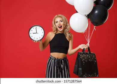 Cheerful young woman girl in black clothes posing isolated on red background studio portrait. Shopping discount sale concept. Mock up copy space. Holding air balloons package bag with purchases clock