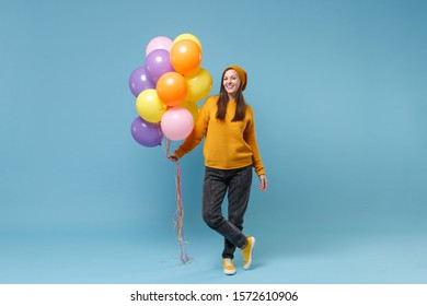 Cheerful young woman girl in sweater hat posing isolated on blue background studio portrait. Birthday holiday party people emotions concept. Mock up copy space. Celebrating hold colorful air balloons