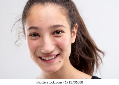 Cheerful young woman grinning at the camera with a happy expression in a close up cropped head shot on white