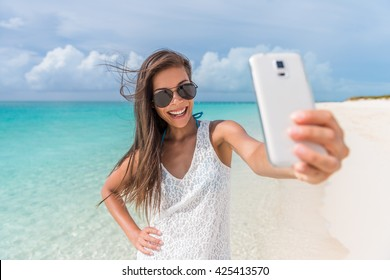 Cheerful young woman having fun taking smartphone selfie pictures of herself on tropical beach travel Caribbean holidays. Happy Asian girl model wearing fashion aviator sunglasses. Summer lifestyle.