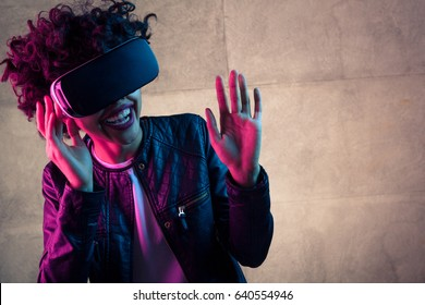 Cheerful young woman having the VR experience with hands up at the gray concrete wall.