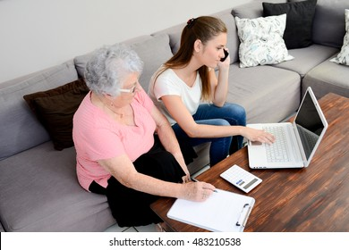 cheerful young woman helping an old person doing paperwork and telephone call