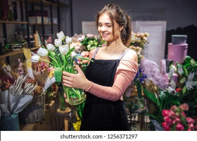 Cheerful young woman hold glass flower vase with white tulips. She smiles. Florist stand in flower shop.