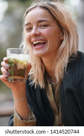 Cheerful young woman holding a cocktail grass outdoors