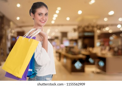 Cheerful young woman holding colorful shopping bags over Shopping malls background. Happiness, consumerism, sale and people concept.