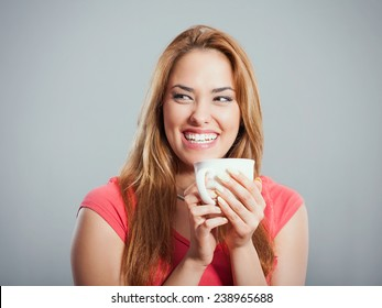 Cheerful young woman holding cup of tea or coffee. Studio Shot