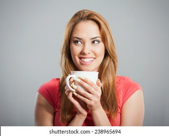Cheerful young woman holding cup of hot drink