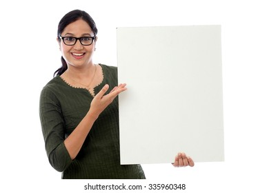 Cheerful young woman holding empty white board