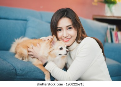 Cheerful young woman holding her puppy with black nose. Indoor portrait of smiling girl with dark long hair posing with dog on rose pink color background and blue sofa at home.