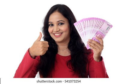 Cheerful young woman holding Indian currency with thump up gesture