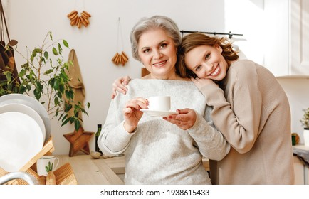 Cheerful young woman hugging elderly mother drinking tea and looking at camera  in the cozy kitchen at home