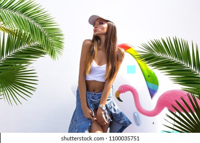 Cheerful young woman in jeans jacket and cap at beach. Happy smiling girl enjoying the beach and looking at camera. Latin tanned woman feeling good and having fun during summer vacation.Miami,beach