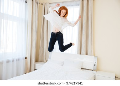 Cheerful young woman jumping on the bed at home