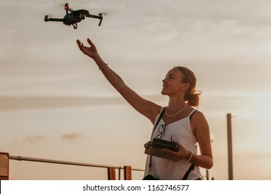 Cheerful young woman landing a drone on her hand by the seaside, holding remote control in her hard, sunset in the background
