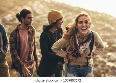 Cheerful young woman laughing while hiking with social networking friends. Female enjoying hiking with her friends.