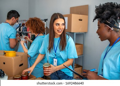 Cheerful young woman laughs along with her friend while volunteering in a community food bank. They are sorting through food donations. Volunteers are working in the background