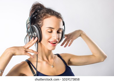 Cheerful young woman listening music with headphones, on white