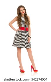 Cheerful young woman with long brown hair posing in black and white striped dress and high heels. Full length studio shot isolated on white.