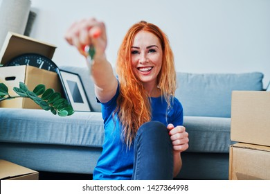 Cheerful young woman looking at camera and showing keys to new apartment