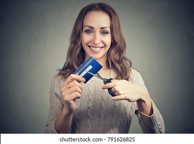 Cheerful young woman looking happily at camera done with credit cards.