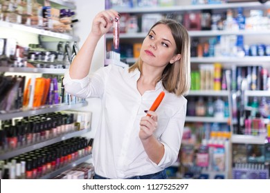 Cheerful young woman looking for new mascara in cosmetics store