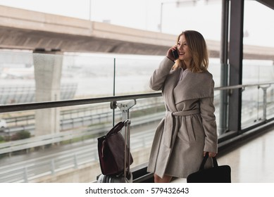 Cheerful young woman with luggage talking phone near the window.