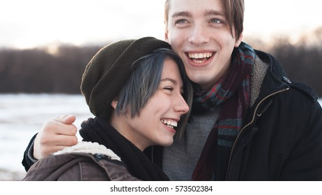 A cheerful young woman and man outdoors at winter. Close up