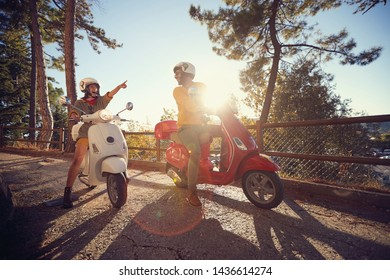 Cheerful young woman and man traveling on motorcycle and looking at Italy on journey.