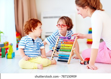 cheerful young woman, mother playing games with kids at nursery room