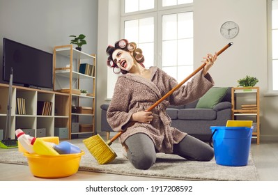 Cheerful young woman with musical talent having fun while cleaning her house. Funny crazy housewife in hair curlers and face mask tidying up home, singing loud songs and playing on pretend mop guitar