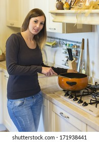 cheerful young woman  on modern kitchen with landle and pot