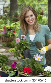 Cheerful young woman planting flowers in her garden