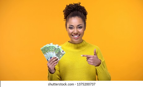 Cheerful young woman pointing at euro bills in hand, bank investment, cashback