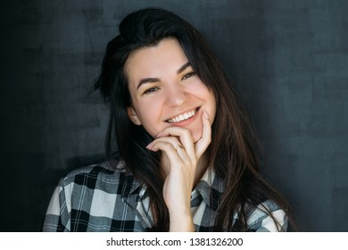 Cheerful young woman portrait. Smiling beautiful brunette looking curiously. Hand at chin. Coquettish inquisitive lady.