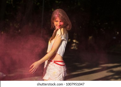 Cheerful young woman posing with pink powder Holi exploding around her