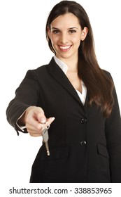 A cheerful young woman presenting a key. Focus is on her face.