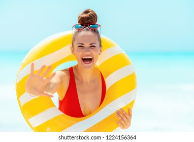 cheerful young woman in red beachwear with yellow inflatable lifebuoy on the seacoast