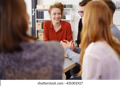 Cheerful young woman in red shirt listening to coworkers discuss something during meeting around large table in small office