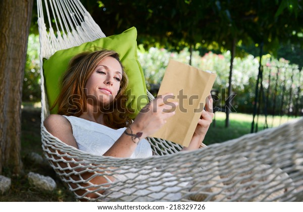cheerful young woman relaxed reading a book in a hammock in a peaceful garden during summer holiday