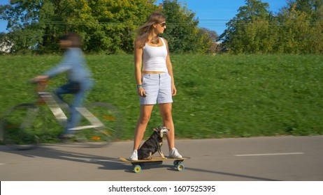 Cheerful young woman rides an electric longboard with her miniature pinscher dog. Caucasian woman enjoys a fun cruise on e-skateboard with her adorable little puppy. Modern girl riding an e-longboard.
