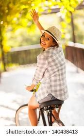 cheerful young woman riding her bike waving goodbye