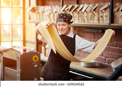 Cheerful young woman rolling a knead through pasta machine and smiling. Making pasta. Making pasta in restaurant. Woman rolling dough in cafe