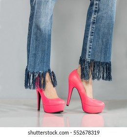 Cheerful young woman with sexy legs wearing jeans and high heels